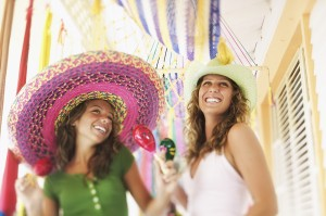 Smiling women with sombreros and maracas